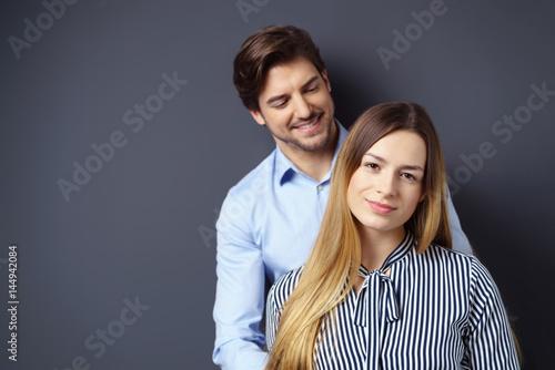 junges paar steht vor einer grauen wand Poster