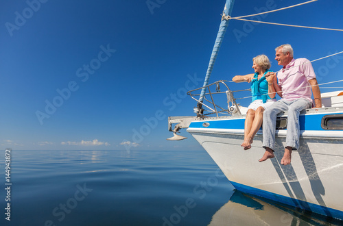 Happy Senior Couple Sitting on the Side of a Sail Boat Poster