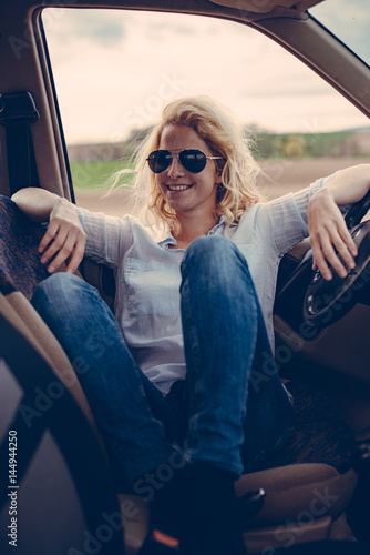 Poster Female driver sitting in off road vehicle on road trip