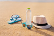 Quadro Vacation concept. Essentials on the sea beach. Bottle of drinking water, sunglasses, hat, flip-flops.