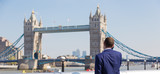 Businessman talking on mobile phone outdoor, looking at Tower Bridge in London city, UK.