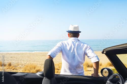 Man on the summer beach near car looking to the sea