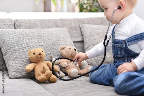 Mädchen untersucht ihre Teddys