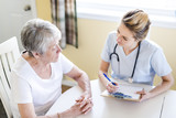 Senior woman with her caregiver at home - 144983402