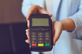 Close up of woman's hands holding payment terminal, toned