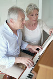 Senior man learning how to play piano with teacher