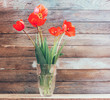 Bouquet of flowers of red tulips in a glass vase on a background of wooden boards close-up