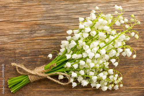 Fotobehang Lelietjes van dalen Vintage bouquet of wild flowers, the white scented lilies of the valley on an old wooden plank closeup