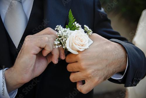 Dettaglio di abito da sposo in cui lo sposo si sistema il fiore nella giacca