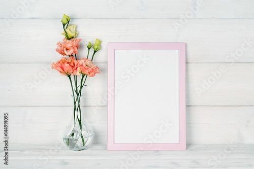 Flowers in vase and a photo frame on a wooden background. Poster
