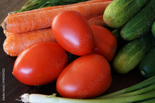 Colorful close up photo of vegetables as cucumbers, carrots, oval tomatoes, dill and long white bunching evergreen onion from garden on the dark wood finish table © Iryna