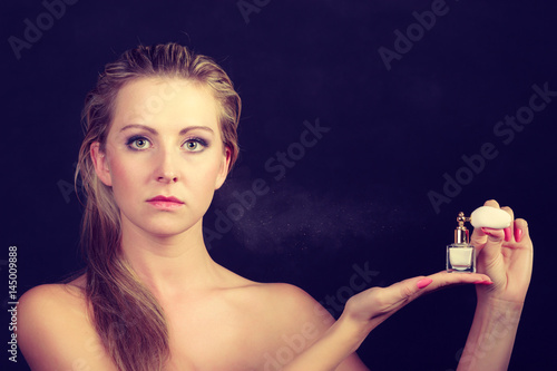Plakat Beautiful woman with holding and applying perfume