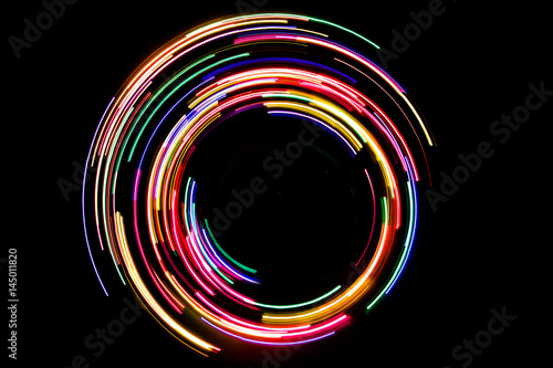 Abstract rotating neon lights texture with black empty copy space inside.