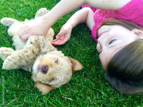 Poster Girl playing with puppy in the lawn