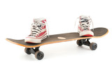 Used skateboard and gumshoes on white background