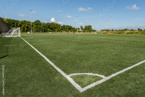 Fototapeta Soccer field background with a shallow depth of field on a beautiful summer day
