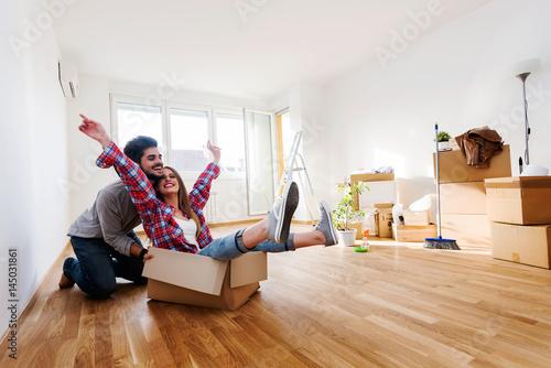 Leinwandbild Motiv Happy young couple moving in new home unpacking boxes