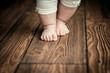 Leinwanddruck Bild - Baby feet doing the first steps. Baby's first steps.