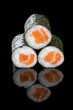 Sushi maki with salmon, on a black background with reflection. Asian food