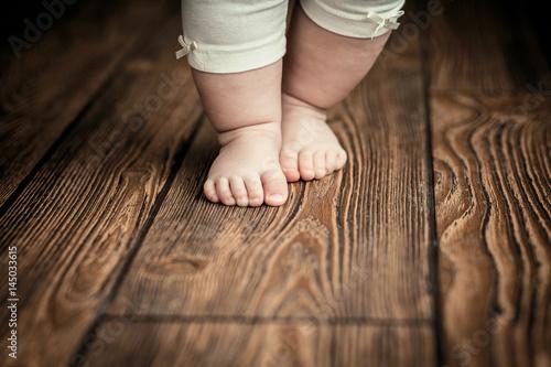 Leinwanddruck Bild Baby feet doing the first steps. Baby's first steps.