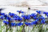 Blue flowers, summer wildflowers on wooden background, overhead