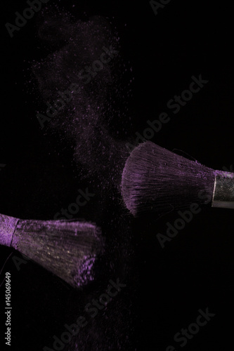 Poster Make up brush with purple dust on black background