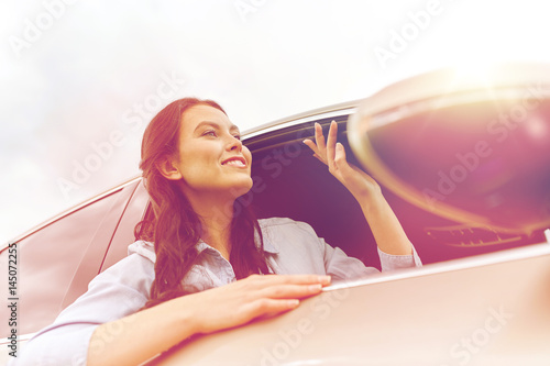 happy young woman driving in car - 145072255