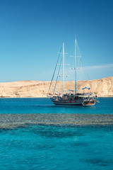 Sail boat in the coral sea near island. Summer vacation in an exotic country. Red sea with clear turquoise water.