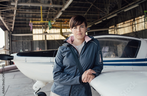 Plakat Female pilot posing in the hangar