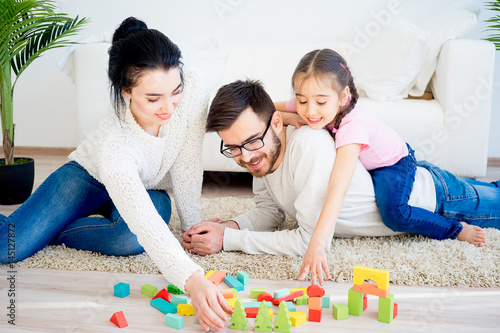 Family playing with toy blocks Poster