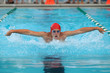Male competitive swimmer swimming the butterfly stroke in a meet