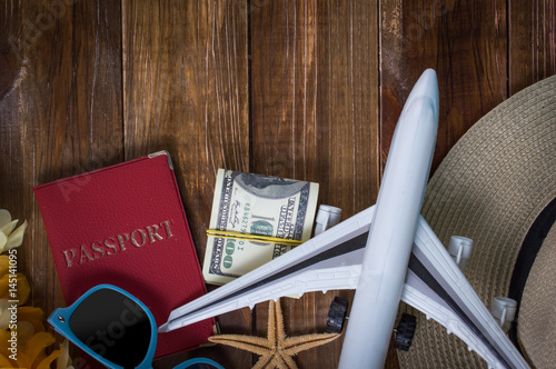 Passport, airplane, glasses on a wooden background. Travel concept