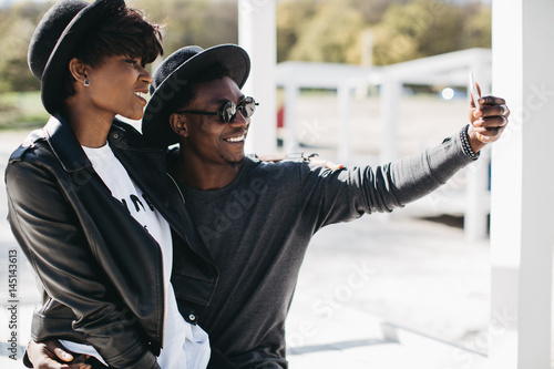 Poster A beautiful and stylish young african couple in sunglasses and hats embracing and making selfie on a outdoor of summer