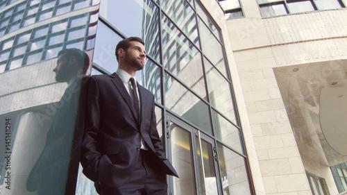 Confident delighted businessman standing near entrance door