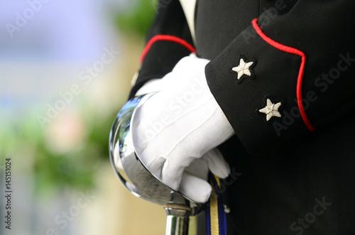 Carabiniere vestito in alta uniforme tiene con due mani la spada Poster