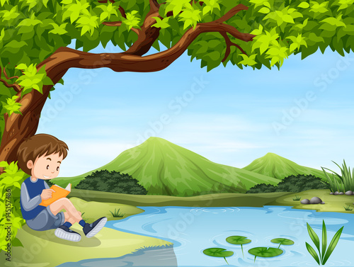 Keuken foto achterwand Lime groen Boy reading book by the pond