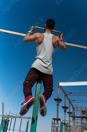 Young bodybuilder doing pull up exercise on bar Poster