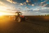 Farmer with tractor seeding - sowing crops at agricultural field in spring