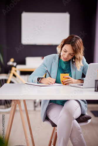 Businesswoman writing down notes while sitting in personal work space Poster