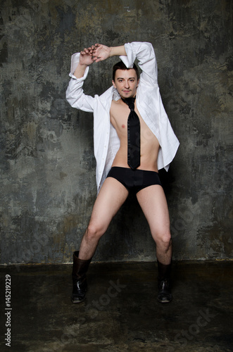 Young attractive guy dancing. White shirt and black tie. Poster