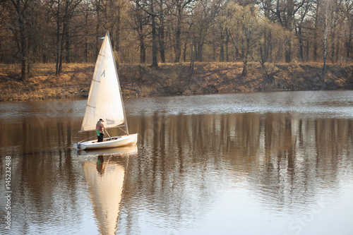 GOMEL, BELARUS - 9 April 2017: A small boat with a sail swims along the river in Poster