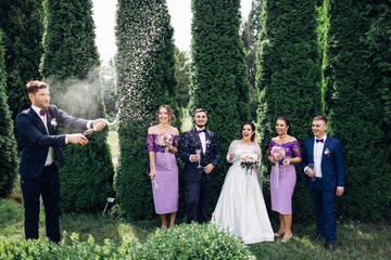 The brides,bridesmaids and groomsmen opening a bottle of champagne