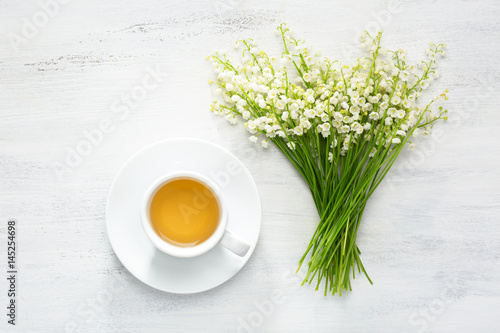 Fotobehang Lelietjes van dalen Cup of tea and bouquet of Lilies of the Valley on rustic table.
