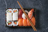 Sushi Set nigiri and sushi rolls in plastic food delivery box with chopsticks over black stone texture background. Top view with space. Japan menu