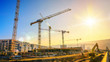 Leinwanddruck Bild - Large construction site including several cranes working on a building complex, with clear blue sky and the sun