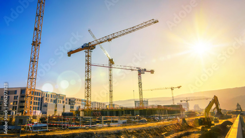 Leinwanddruck Bild Large construction site including several cranes working on a building complex, with clear blue sky and the sun