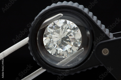 loose brilliant round diamonds is being held by tweezers and looked through a bl Poster