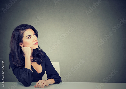 Thinking business woman sitting at desk Poster