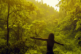 Man stays with his back in front of jungle and raise his hands to the sides. Freedom concept