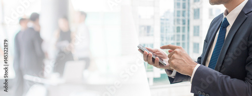 Business man using smart phone in office space background and copy space.